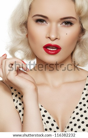 Fashion portrait of beautiful woman model with red lips make-up and long curly blond hair. Pin-up retro style. Pretty blond coquette model in vintage dress with peas print. - stock photo