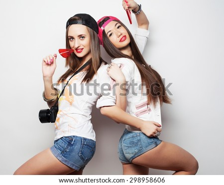 Fashion portrait of two young pretty hipster girls wearing bright make up and holding candys. Studio portrait of two cheerful best friends sisters having fun and making funny faces. - stock photo