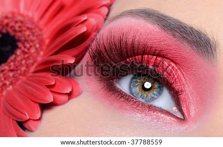 fashion woman eye with red make-up and long false eyelashes -  flower at background - stock photo