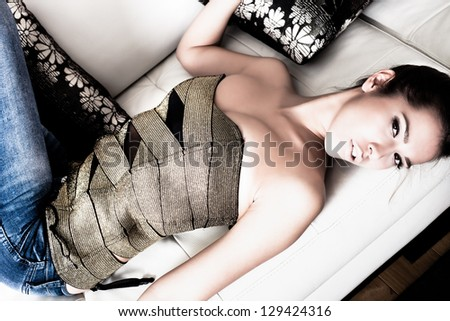fashion young woman lie on white  leather bed indoor shot