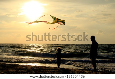 father and daughter flying kite at beach - stock photo
