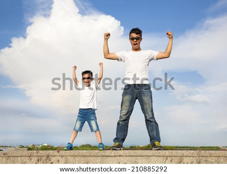 father and son standing  and raising hands   - stock photo