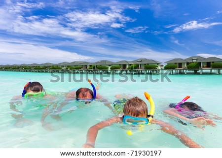 Father snorkeling in sea with three young children, stilt huts or houses in background, Maldives.