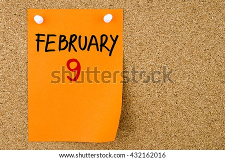 9 FEBRUARY written on orange paper note pinned on cork board with white thumbtacks, copy space available - stock photo