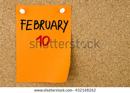 10 FEBRUARY written on orange paper note pinned on cork board with white thumbtacks, copy space available - stock photo
