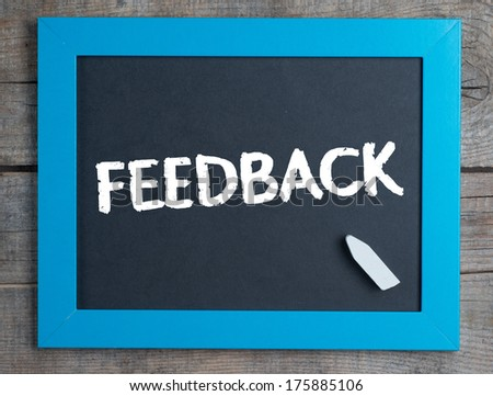 Feedback. Creative composition with the message Feedback on blackboard on wooden table - stock photo