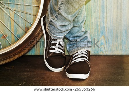 feet in jeans and sneakers alongside a bicycle - stock photo