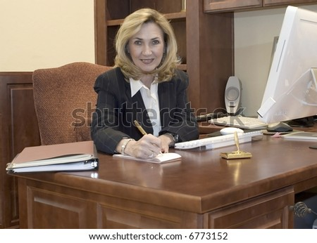 female business executive sits at her desk writing - stock photo