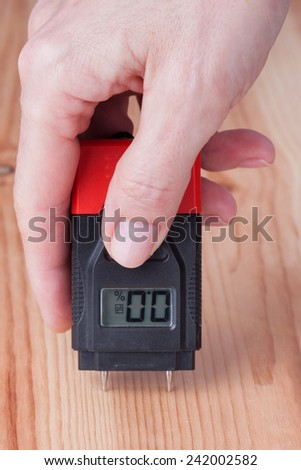 Female hand measuring moisture in wooden wall - stock photo