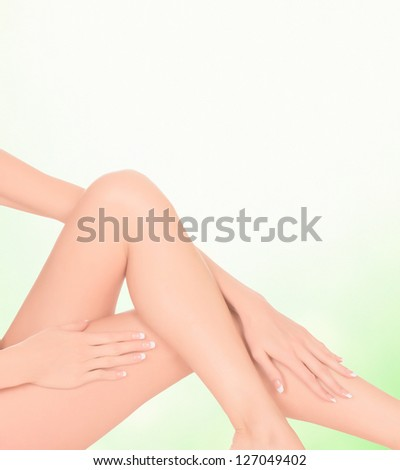 Female legs on green blurred background with a place for your info