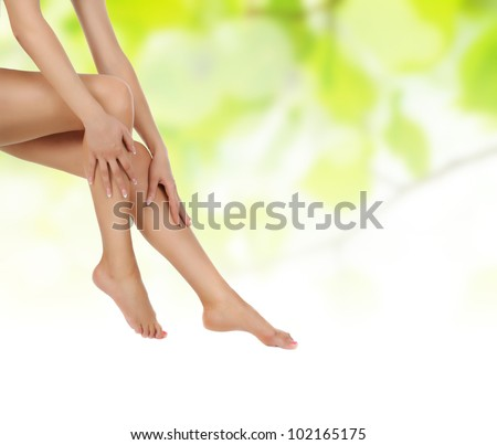 female legs over green natural background being massaged with hands - heathcare and hygiene concept