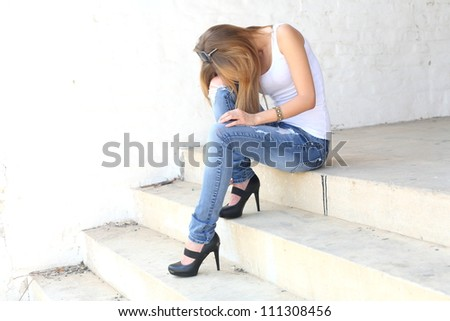 female sitting on the stairs in depression state - stock photo