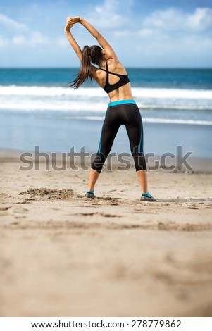Female stretching arms and breathing exercises in morning at beach - stock photo