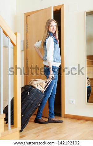female tourist with luggage near door in home