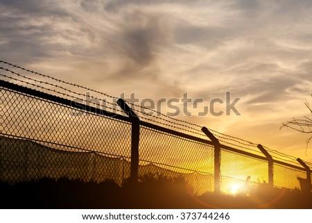 Fences and sunset - stock photo