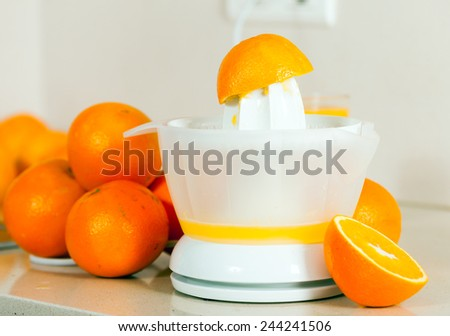 few oranges near the hand juicer on   table. - stock photo