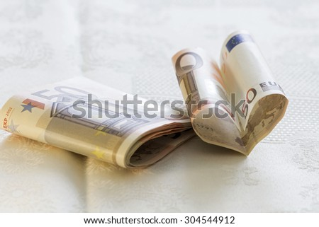 Fifty euro banknotes and one in the form of a heart  - stock photo