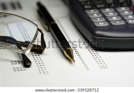 Finance analysis concept using finance report with pen, riding glasses and calculator - stock photo