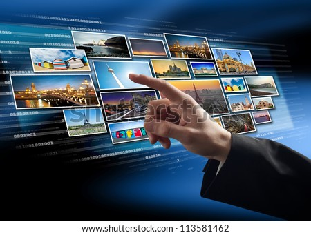 Finger pushing picture/button on a virtual touch screen interface - stock photo