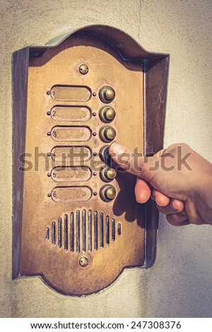 Finger ringing a door bell - vintage. - stock photo