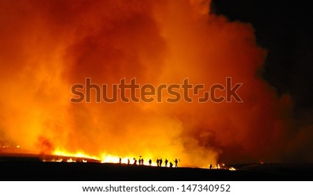 Firefighters tend a grass fire at night in the Drakensberg foothills, Underberg, South Africa