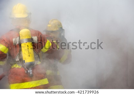 2 firemen in operation surround with smoke - stock photo