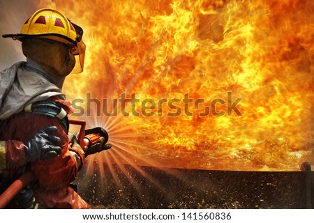 Firemen using extinguisher and water from hose for fire fighting at firefight training of insurance group. Firefighter wearing a fire suit for safety  under the danger case.