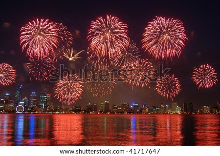 Fireworks over city with reflection in river - stock photo