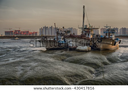 Fishing boats dock at low tide. - stock photo