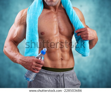 Fitness  Athletic Man holding bottle of water and towel - stock photo
