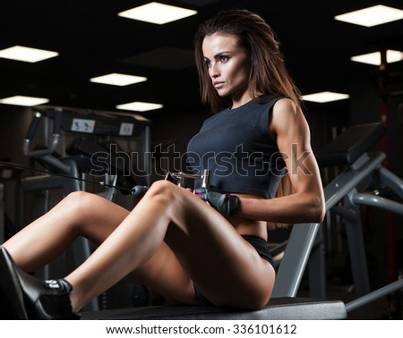 Fitness woman in sport wear with perfect fitness body resting in gym - stock photo