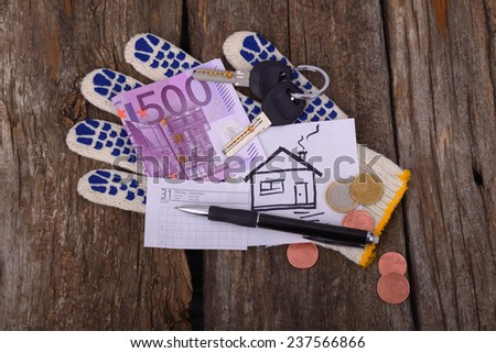 five hundred euros painted house and car keys at work glove pen and a piece of paper to write on old wooden table - stock photo