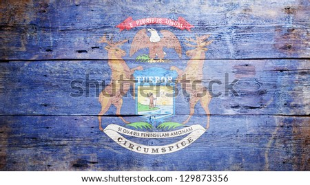 Flag of the State of Michigan painted on grungy wooden background - stock photo