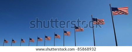 11 flags in a row with a beautiful blue sky - stock photo