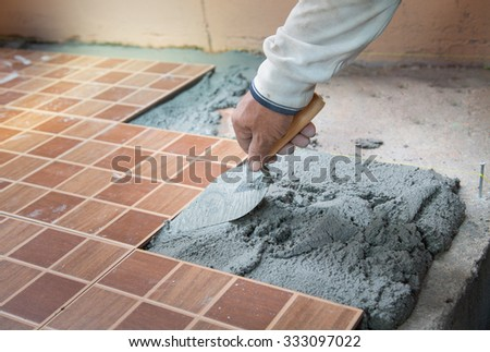 floor tiling by manual worker - stock photo