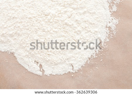 flour on beige paper - white food background