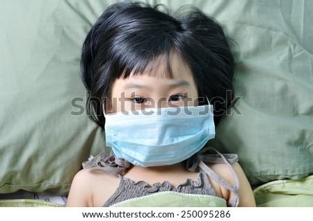 Flu illness little asian girl under blanket in medicine health-care mask - stock photo