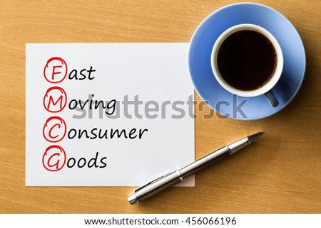 (FMCG) Fast Moving Consumer Goods- handwriting on notebook with cup of coffee and pen, acronym business concept