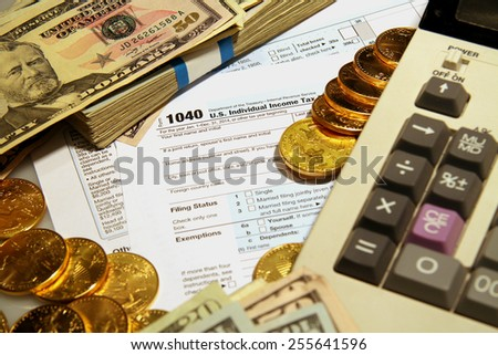 1040 form with gold money calculator pencil and eraser - stock photo