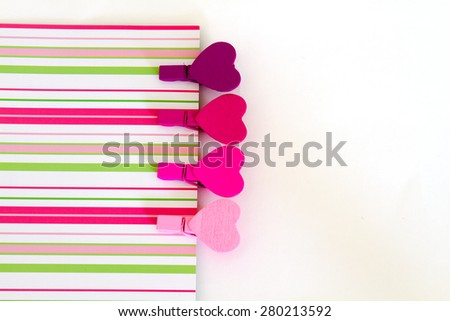 Four colorful wooden pegs in the form of heart on paper stripes. pink tone - stock photo