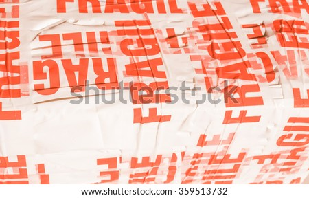 Fragile warning label on tape on a packet parcel for mail post shipping vintage - stock photo