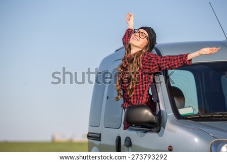 Freedom car travel concept - woman relaxing out of window in a car over blue sky background. Girl relaxing enjoying free holidays road trip. soft daylight
