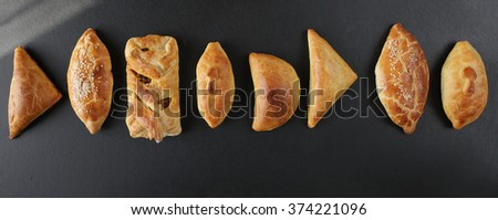 Fresh baked pasties filled with vegetables ,chicken,meat and mushroomson dark background