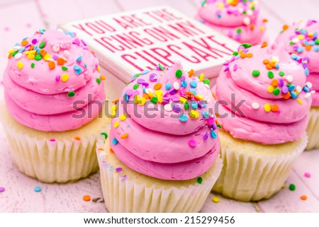 5 fresh baked vanilla cupcakes with pink swirled strawberry frosting topped with colorful sprinkles and wooden box with words on top