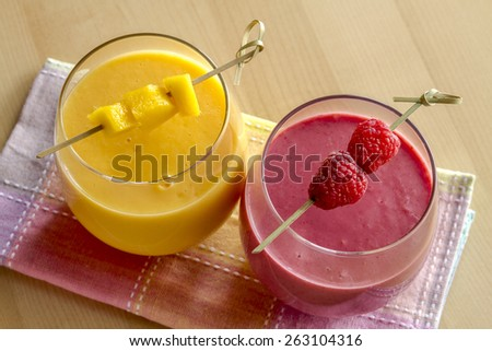 2 fresh blended fruit smoothies made with mango, orange, cantaloupe, raspberries, and strawberries garnished with fruit pieces from above - stock photo