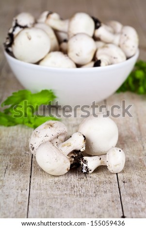 fresh champignons with parsley in a bowl on rustic wooden table