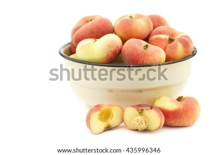 fresh colorful flat peaches (donut peaches) in an enamel bowl on a white background - stock photo