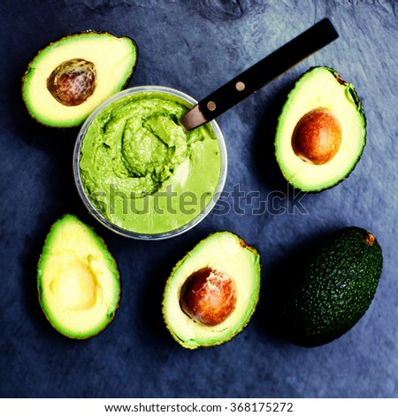 Fresh green avocado and guacamole. Food background with fresh organic avocado on old wooden table, top view, copy space - stock photo