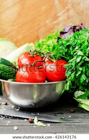 Fresh juicy ripe summer useful vegetables and greens, red tomatoes , cucumbers , cabbage , lettuce , basil , parsley , dill and salt and spices on a dark wooden background