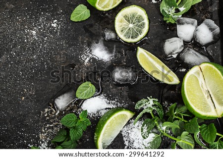 Fresh mint, limes, ice, sugar for mojito over old black surface. Top view.  - stock photo